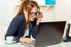Piękna sekretarka ostrożnie skanuje emaila na komputerze zdjęcia stock