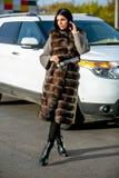 Piękna seksowna brunetka w okularach przeciwsłonecznych i futerkowego żakieta spacery zestrzelamy ulicę na słonecznym dniu i spoj zdjęcie stock