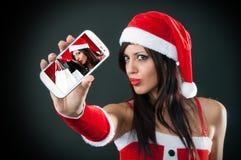 Piękna seksowna dziewczyna jest ubranym Santa Claus odziewa z mądrze telefonem Obraz Royalty Free