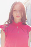 Piękna seksowna dziewczyna w czerwonej sukni z delikatnym spojrzeniem w słońce przy zmierzchem w jaskrawym słonecznym dniu Zdjęcia Royalty Free