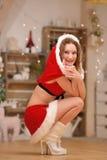 Piękna seksowna dziewczyna z kędzierzawym włosy w Święty Mikołaj odziewa kucnięcia obraz royalty free