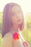 Piękna seksowna dziewczyna z tłuściuchnymi wargami z makowym kwiatem w ręce z ogołacającymi ramionami przy zmierzchem w polu w św Obraz Stock