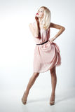 Piękna seksowna elegancka uderzająca blondynki kobieta z jaskrawym makeup w menchiach ubiera z dlinnymi nikłymi nogami w studiu n Zdjęcie Stock
