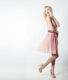 Piękna seksowna elegancka uderzająca blondynki kobieta z jaskrawym makeup w menchiach ubiera z dlinnymi nikłymi nogami w studiu n Zdjęcia Royalty Free