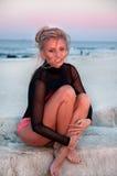 Piękna seksowna kobieta w eleganckim czarnym swimsuit obsiadaniu na skałach blisko morza Zdjęcie Stock