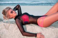 Piękna seksowna kobieta w eleganckim czarnym swimsuit obsiadaniu na skałach blisko morza Obrazy Stock