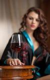 Piękna seksowna kobieta z szkłem wina obsiadanie na krześle. Portret kobieta z długim kędzierzawym włosy pozuje rzucać wyzwanie Obrazy Stock