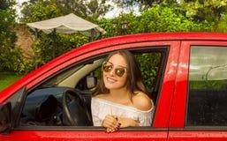 Piękna seksowna młoda kobieta jest ubranym słońca szkła i pozuje dla kamery w czerwonym samochodzie Zdjęcia Royalty Free