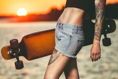 piękna, seksowna modniś dziewczyna w tatuaży stojakach z longboard przeciw zmierzchowi, Zdjęcia Stock