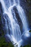 Piękna siklawa spada kaskadą nad skałami z miękkim eterycznym błękitnym brzmieniem obraz stock