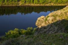 Piękna skała na rzece, iluminującej światłem słonecznym Obrazy Stock