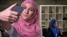 Piękna skupiająca się twarz arabska kobieta w różowym hijab bierze obrazki odizolowywających od jej pracujących kolegów w cegle