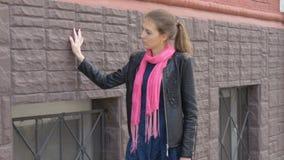 Piękna smutna dziewczyna chodzi wzdłuż ulicy wzdłuż domu Odbija na smutnej wiadomości Smucenie i upragnienie zbiory wideo