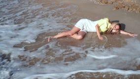 Piękna, smutna dziewczyna w białej sukni, i długi blondynu lying on the beach na piasku z jej oczami zamykającymi przy, zbiory wideo