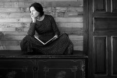 Piękna smutna kobieta siedzi z książką na starej czarnej klatce piersiowej na drewnianym tle fotografia stock
