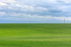 Piękna spokojna łąka pod łagodnym chmurnym niebem i linia energetyczna przy horyzontem Zdjęcia Stock