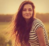 Piękna spokojna uśmiechnięta młoda kobieta patrzeje szczęśliwy z długim jaskrawym włosy na natura zmierzchu lata jaskrawym tle zb obraz stock
