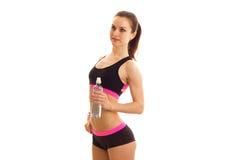 Piękna sport dziewczyna w krótkich skrótach i wierzchołku stoi z ukosa butelkę woda i trzymać Fotografia Stock