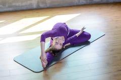 Piękna sportowa młoda kobieta robi joga pozie Parivrtta Janu Sirsasana rozciąga Pilate zdjęcia royalty free