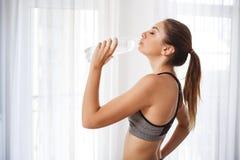 Piękna sprawności fizycznej dziewczyny woda pitna od plastikowej butelki Fotografia Royalty Free