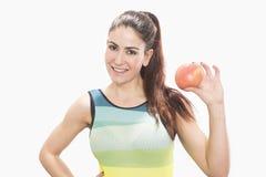 Piękna sprawności fizycznej kobieta z czerwonym jabłkiem obraz royalty free
