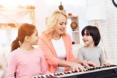 Piękna starsza kobieta uczy małych wnuków bawić się syntetyka Zdjęcie Royalty Free