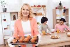 Piękna starsza kobieta w różowej bluzce piec babeczki dla wnuków które jedzą obiad w kuchni Zdjęcia Stock