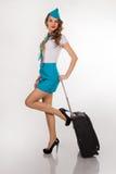 Piękna stewardesa trzyma bagaż obraz stock