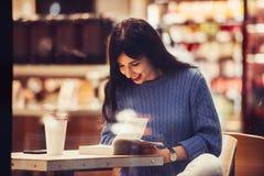 Piękna studencka kobieta czyta książkę w kawiarni z ciepłym wygodnym wnętrzem i pije kawę fotografia stock