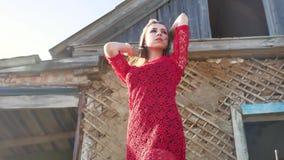 Piękna styl życia dziewczyna w czerwonej sukni Seksowna dziewczyna w sukni stoi obok starego domu ruiny Zdjęcia Stock