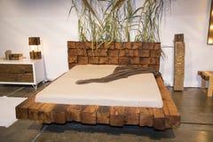 Piękna sypialnia z drewnianym łóżkiem przy meblarskim jarmarkiem Obrazy Stock