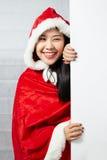 Piękna szczęśliwa azjatykcia dziewczyna w Święty Mikołaj odziewa Fotografia Stock