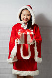 Piękna szczęśliwa azjatykcia dziewczyna w Święty Mikołaj odziewa Fotografia Royalty Free