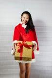 Piękna szczęśliwa azjatykcia dziewczyna w Święty Mikołaj odziewa Obrazy Stock
