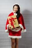 Piękna szczęśliwa azjatykcia dziewczyna w Święty Mikołaj odziewa Zdjęcia Stock