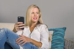 Piękna szczęśliwa blond kobieta wczesny 40s relaksował w domu żyć pokój używać internetów ogólnospołecznych środki na telefonu ko fotografia stock