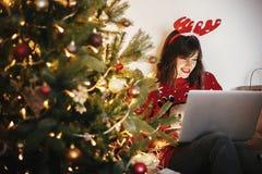 Piękna szczęśliwa dziewczyna siedzi z laptopem przy w reniferowych poroże zdjęcie royalty free