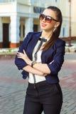 Piękna, szczęśliwa dziewczyna w biznesu stylu, jest w mieście jest ubranym okulary przeciwsłonecznych w kurtce obrazy stock