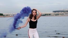Piękna szczęśliwa elegancka seksowna młoda dziewczyna przy nadmorski chwytem światło w górę barwionych dymnych bomb swobodny ruch zbiory