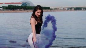 Piękna szczęśliwa elegancka seksowna młoda dziewczyna przy nadmorski chwytem światło w górę barwionych dymnych bomb swobodny ruch zbiory wideo