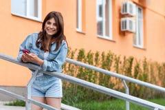 Piękna szczęśliwa młoda brunetki kobieta w drelichowej przypadkowego stylu pozycji, mienie dalej na piętrze, jej mobilny smartpho fotografia stock