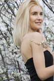 Piękna szczęśliwa młoda kobieta cieszy się odór w kwiatonośnym wiosna ogródzie Obrazy Stock