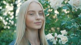 Piękna szczęśliwa młoda kobieta cieszy się odór wiosny kwiatonośnego ogród zbiory