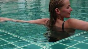 Piękna szczęśliwa młoda kobieta w okularach przeciwsłonecznych uśmiechniętych i relaksują w hotelowym basenie zbiory