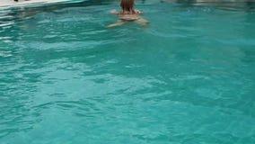 Piękna szczęśliwa młoda kobieta w okularach przeciwsłonecznych uśmiechniętych i relaksują w hotelowym basenie zdjęcie wideo