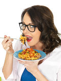 Piękna Szczęśliwa Młoda Latynoska kobieta Je talerza pomidoru i basilu Fusilli makaron obrazy royalty free