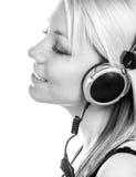 Piękna szczęśliwa nastoletnia dziewczyna słucha muzyka przez hełmofonów fotografia royalty free