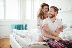 Piękna szczęśliwa para budzi się up ono uśmiecha się w sypialni Zdjęcie Royalty Free