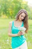 Piękna szczęśliwa uśmiechnięta dziewczyna z długimi dandelions w rękach skróty i koszulka jest odpoczynkowa w parku na słonecznym obrazy stock