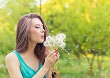 Piękna szczęśliwa uśmiechnięta dziewczyna z długimi dandelions w rękach skróty i koszulka jest odpoczynkowa w parku na słonecznym Zdjęcie Royalty Free